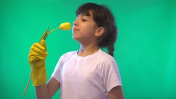 Dívka na zeleném pozadí. Na rukou žluté rukavice. žlutý Tulipán. Pozitivní emoce. Vděčnost. Bílá košile. Zelené pozadí. Video v 4k.