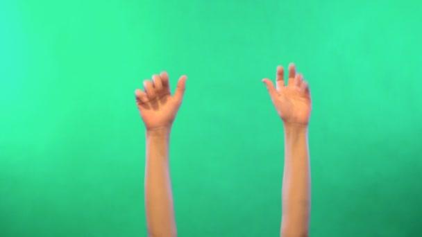 Gyermekek kezek zöld háttérrel. Mozgás a levegőben. Világos bőr. Lány teste. Nélkül egy arc. A videó 4k.
