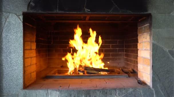 V kamenné troubě hoří jasný oheň. Pec je vyrobena z bloků. Pálení tmavých uhlí. Velký výhled na oheň. Pouliční situace. Kavárna, restaurace, dům. Žhavější plameny. Video v 4k.