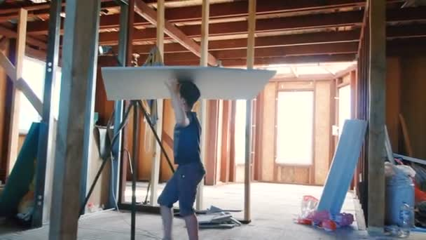 The boy carries on his head a sheet of foam. Work in the house. Construction of a country house. Decoration of the room. Construction Materials. Wooden floors.