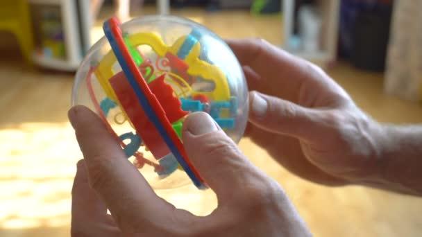 Muž má v rukou plastovou kouli z hraček. Hraní hraček. Fragment člověka. Dětská hádanka. Otec v dětských hrách. Kontrola stavu. Close-up.