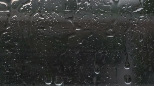 Po skle proudí kapky deště. Tmavé pozadí. Za oknem je špatné počasí. Pruhy vody. Abstraktní pozadí.