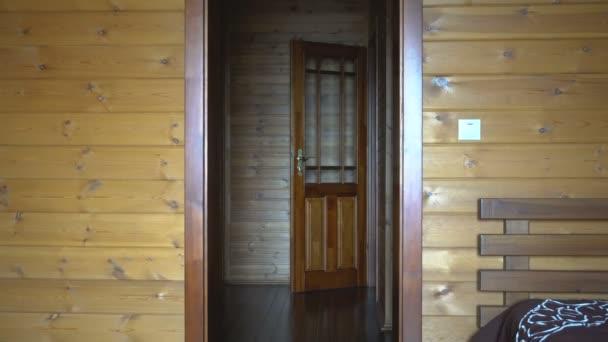 Holzwände des Hauses. Tür auf. Eine männliche Hand aus dem Raum schließt die Tür. Tageslicht. bemalte Platten.