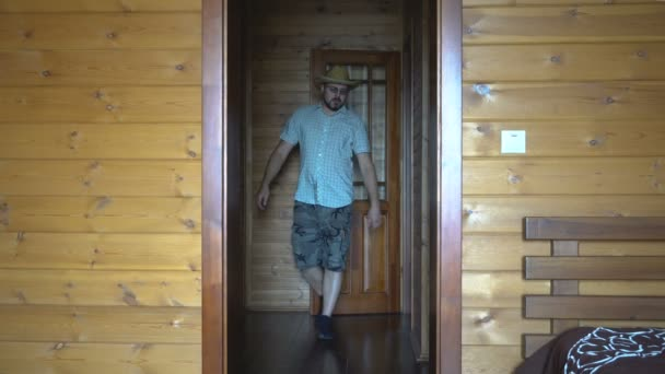 An adult man with a beard sits out of the room. On the head is a straw hat. Doing exercises, warming up. Wooden country house.