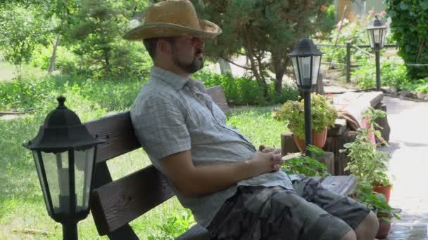 Felnőtt férfi szakállas ül egy padon. A fej egy szalmakalapot. Alszik, és megrázza a fejét. A háttérben egy zöld kert. A vidéki élet. Park tájkép.