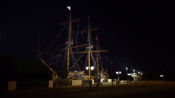 At the pier stands an old wooden ship. Dark night. Light of lanterns. Tall masts. People walk along the shore. General form.