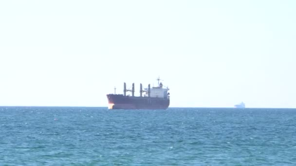 Nákladní lodě plují na moři. Horizont. Tmavě modrá voda. Ekologický problém. Námořní doprava. Transport. Obchod. Mezinárodní vztahy.