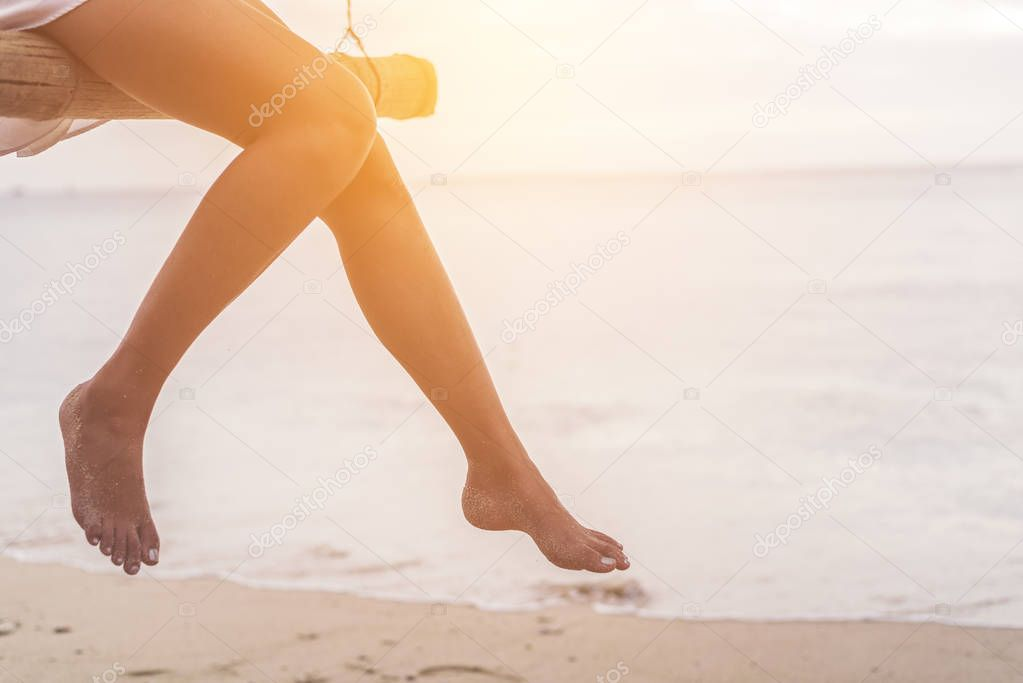 Woman legs at beach on wooden swing. Relax and Single woman concept. Happiness and lifestyle concept. Lonely and sadness concept. Beach and sea theme. Finding soulmate theme. Copy space on right