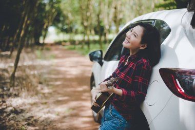 Beauty Asian woman smiling and having fun at outdoors summer with Ukulele near white car. Traveling of photographer concept. Hipster style and Solo woman theme. Lifestyle and Happiness life theme.