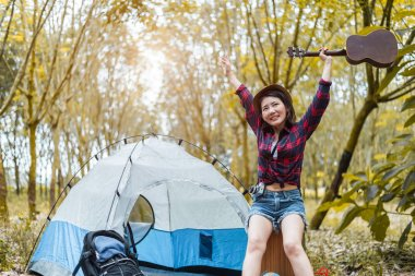 Beauty Asian woman holding guitar and raising hands in forest. Pine woods background. People and lifestyles concet. Camping and travel concept