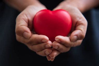 Close up hands giving red heart as heart donor. Valentine day of love concept. Medical ventilator and heart donator charity. Sign of compassion and healthy. Helping hand in freedom life donation