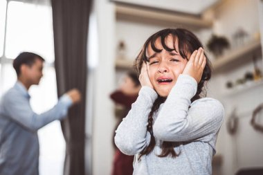 Little girl crying because of her parents quarreling. Girl abused with mother and father shouting and conflict angry background in home. Family dramatic scene, Family social issues problem concept.