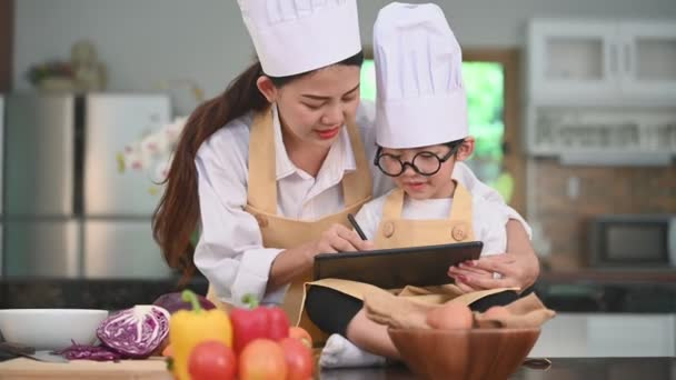 Beautiful Asian woman and cute little boy with eyeglasses prepare to cooking in kitchen at home with tablet. People lifestyles and Family. Homemade food and ingredients concept. Ketogenic salad making