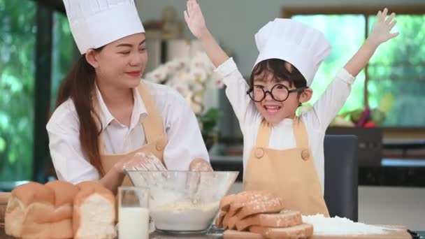 Krásná žena a roztomilá malá Asijská chlapečka s brýlemi, šéfkuchařkou a zástěrkou, která si užívá pekárny v domácí kuchyni legrační. Domácí jídlo a chléb. Koncepce vzdělávání a učení. Emoční portrét