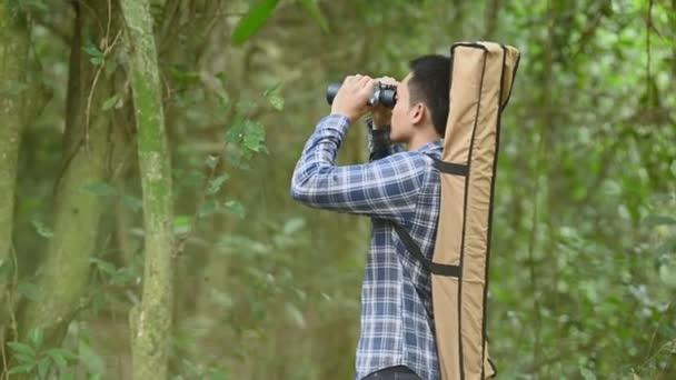 Ember távcső távcső erdőben keresett helyet, mint elveszett emberek vagy előre látható jövőben. Az emberek életmód és szabadidős tevékenység fogalmát. Természet és hátizsákos utazó dzsungel háttér
