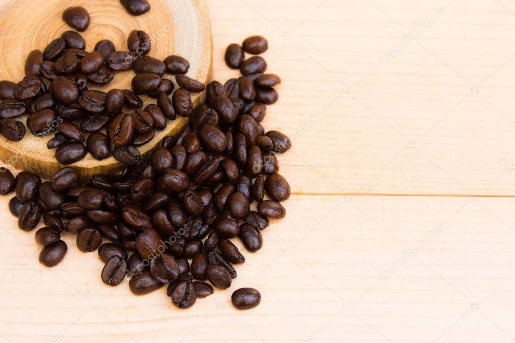 coffee beans over the wood plate on the brown background