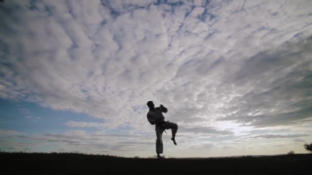 férfi harcművészeti koncepció. egy férfi sziluettje napnyugtakor, aki harcművészetet folytat.
