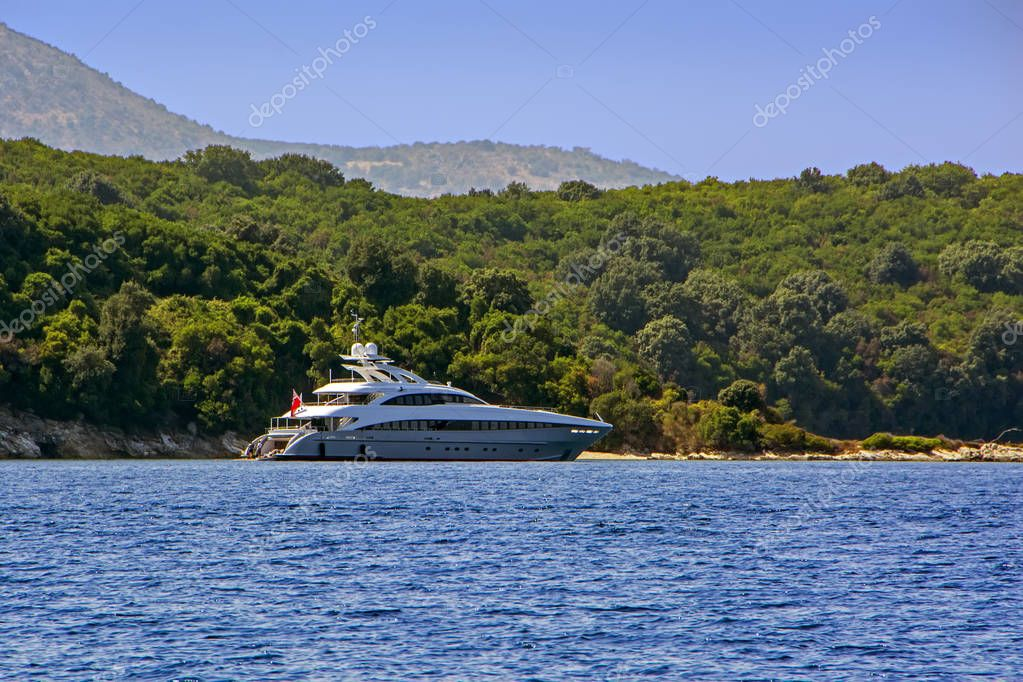 Luxury modern yacht moored in blue sea bay of Corfu Island, Greece with green trees on background