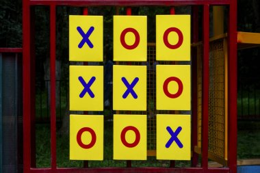 Bright yellow triangular prisms with red zeros and blue crosses for game tic-tac-toe are in red frame on background of playground