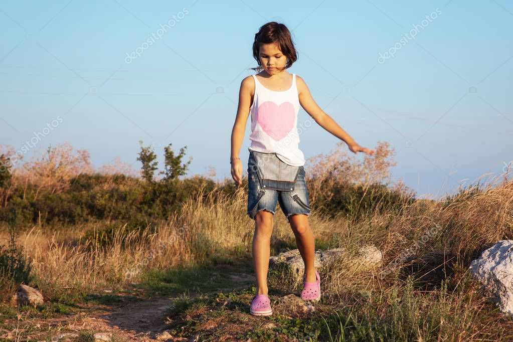 little girl walking on coast at sunny day