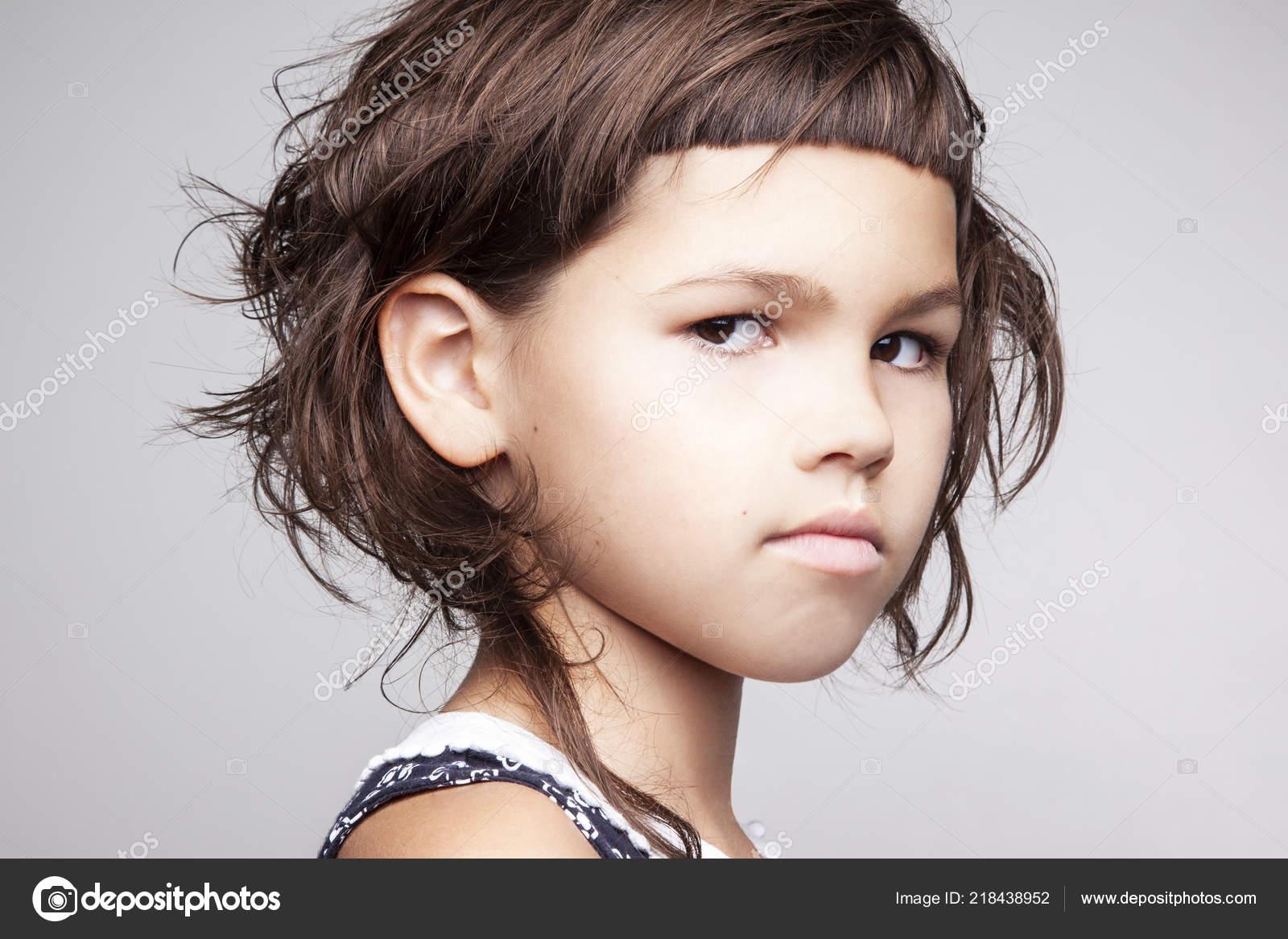 Portrait serious little girl stylish hairdo looking camera isolated white stock photo