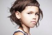 Fotografia Ritratto di bambina seria con pettinatura alla moda che guarda lobbiettivo isolato su sfondo bianco, close-up