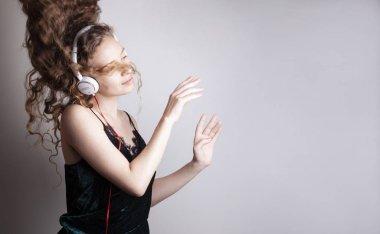 beautiful young woman listening music with headphones in front of white wall and dancing