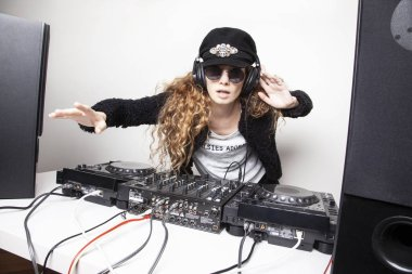 funny redhead woman djing in front of white wall