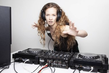 expressive redhead woman djing in front of white wall