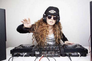 expressive redhead woman in hat and sunglasses djing in front of white wall
