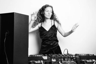 black and white shot of beautiful curly woman dancing while djing in front of white wall