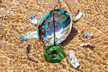 New Zealand - Maori theme - Jade pounamu Koru design pendant with Paua shell laying in tidal shallows on beach - abstract with ripples of water and sunlight