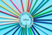 Myšlenku sdílení konceptu, barevné tužky na modrém pozadí