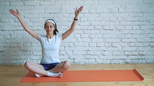 Krásná, inteligentní, sportovní dívka dělá cvičení jógy v tělocvičně v podkroví stylu, s přirozeným světlem velká okna. Na pozadí bílé zdi pro logo.