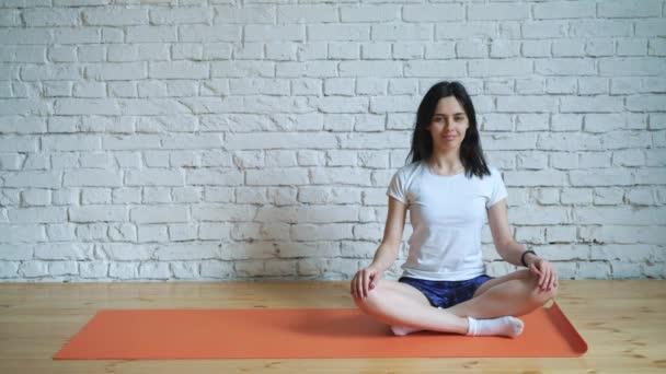 ein schönes, intelligentes, athletisches Mädchen macht Yoga-Übungen in der Turnhalle im Dachgeschoss-Stil, mit natürlicher Beleuchtung durch große Fenster. vor dem Hintergrund eine weiße Ziegelwand für das Logo.