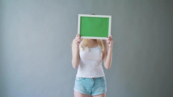 atraktivní žena ukazuje greenkey copyspace s sledování bodů