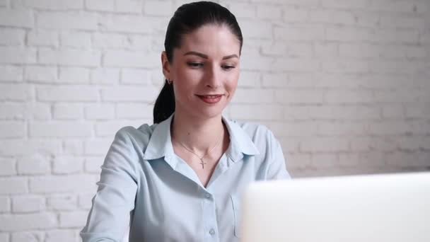 Young business woman working with laptop and thinking about future at open space office in modern interior