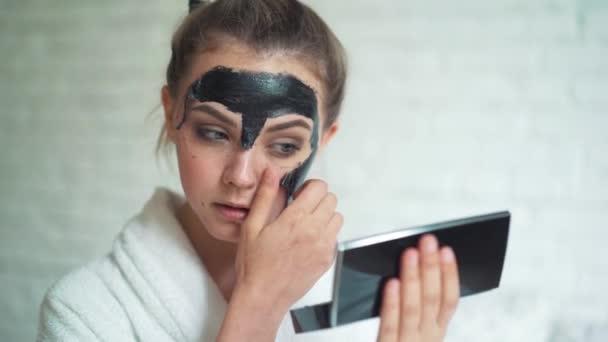 Gyönyörű nő eltávolítja a tisztító maszk a háttér fehér tégla arca.