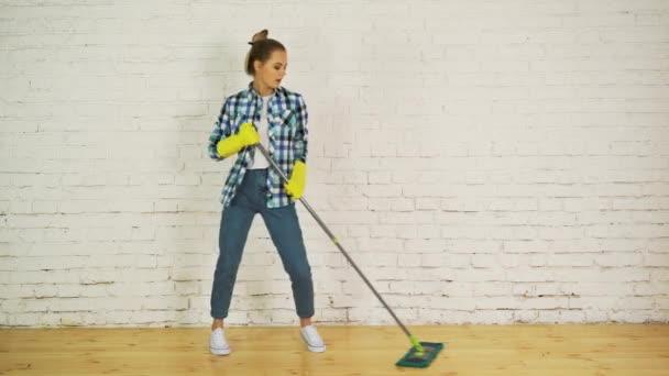 Krásná mladá žena je tanec a usmíval se při čištění podlahy na domácí mopem