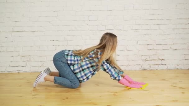 Konzentrierte Frau poliert Holzboden. junges Mädchen in Schutzhandschuhen wäscht Wohnung, Frühjahrsputz-Konzept, Kopierraum