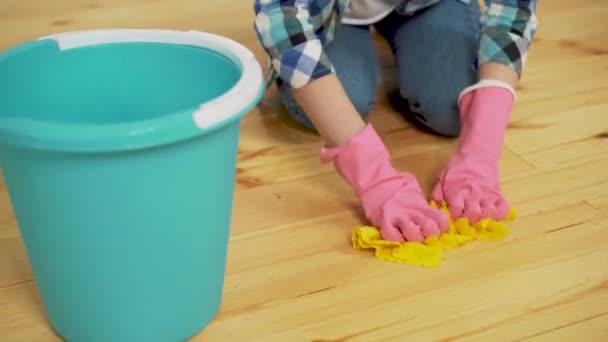 schockierte Frau putzt Haus mit vielen Werkzeugen. junges müdes Mädchen wirft Lappen in einen Eimer.