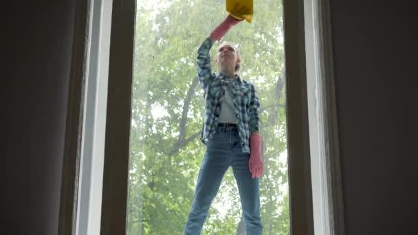 lidé, práce v domácnosti a úklid koncepce - šťastná žena v rukavicích čištění okno s hadr a čistící sprej doma