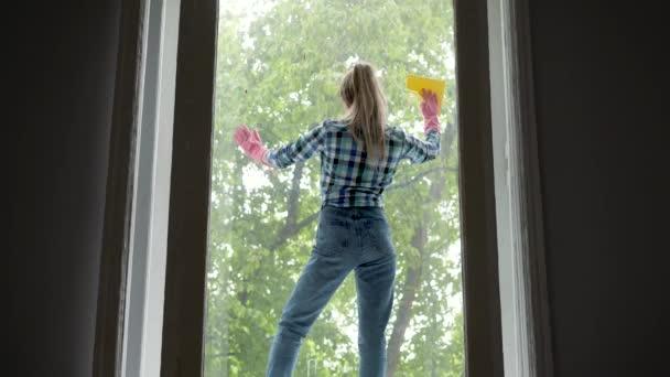Menschen, Hausarbeit und Hauswirtschaftskonzept - glückliche Frau in Handschuhen beim Fensterputzen mit Lappen und Reinigungsspray zu Hause