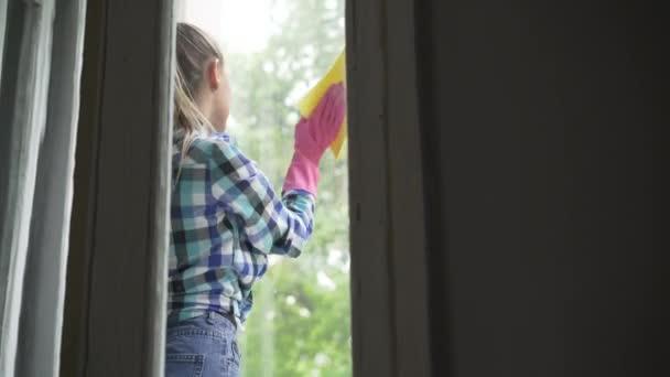 krásná mladá žena mytí okna v pokoji