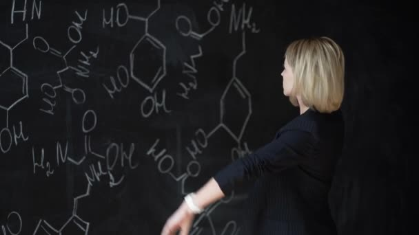 Portrait of a woman solving a difficult task, standing near the Board with formulas. The concept of science. Layout.