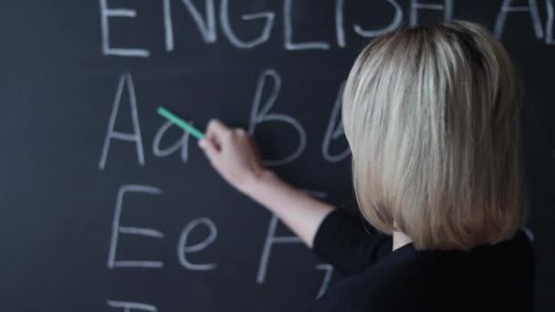 Tanár írásban ábécé betűje krétával táblára. Oktatás-általános iskola-koncepció.
