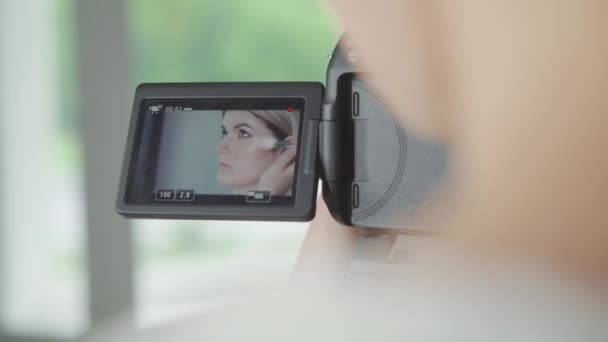 Video operátor. Nadšený mladý nadšený blogger cítil šťastný zároveň sedí u stolu a uvedení na make-up s milá pozorného nahrávání ji na svou kameru