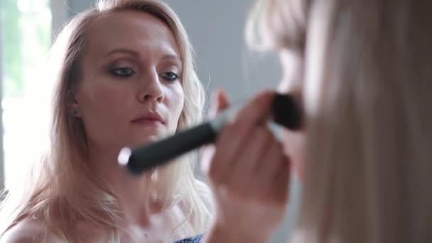 Detail žena použití kosmetické s velkým make-up štětce. Dívky v salonu make-up, použijte prášek na kůži, nadace