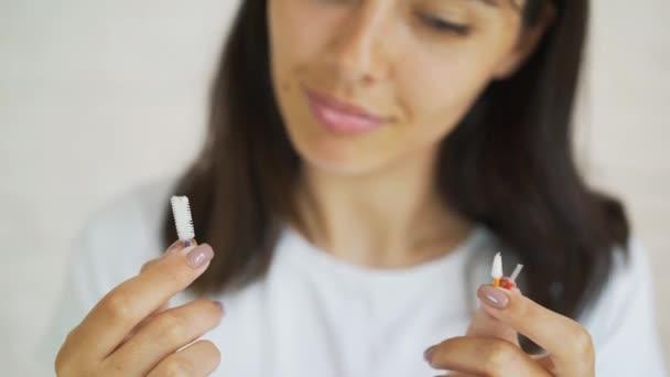 Mundhygiene für Zahnspangen. junges Mädchen mit Zahnspange putzt ihre Zähne. Teenagermädchen putzen und Zähne mit klaren Keramikspangen putzen mit speziellen Putzwerkzeugen.