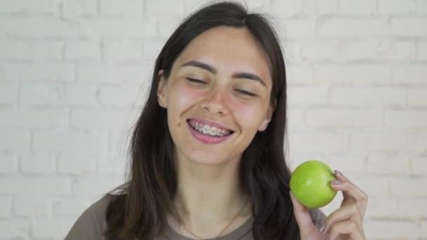 Weibchen mit Klammern an den Zähnen Verzehr von grünem Apfel und Lächeln. Weiß. Closeup